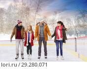 happy friends on outdoor skating rink. Стоковое фото, фотограф Syda Productions / Фотобанк Лори