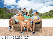 Купить «friends sitting on sofa over seychelles island», фото № 29280127, снято 30 июня 2018 г. (c) Syda Productions / Фотобанк Лори