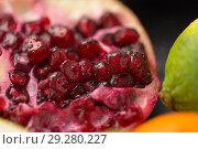 Купить «close up of pomegranate on stone table», фото № 29280227, снято 4 апреля 2018 г. (c) Syda Productions / Фотобанк Лори