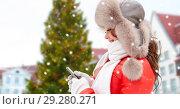 Купить «woman with smartphone over christmas tree», фото № 29280271, снято 7 января 2017 г. (c) Syda Productions / Фотобанк Лори