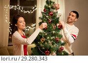 Купить «happy couple decorating christmas tree at home», фото № 29280343, снято 11 января 2018 г. (c) Syda Productions / Фотобанк Лори
