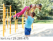 Купить «Man with daughter doing acrobatic elements», фото № 29289475, снято 29 сентября 2018 г. (c) Яков Филимонов / Фотобанк Лори