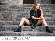 Купить «Young sexy girl tourist in dress sitting at stone stair in center of Barcelona», фото № 29289747, снято 24 сентября 2018 г. (c) Яков Филимонов / Фотобанк Лори