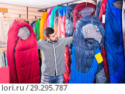 Купить «Buyer is considering the options for sleeping bags», фото № 29295787, снято 8 марта 2017 г. (c) Яков Филимонов / Фотобанк Лори