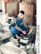 Купить «Worker is choosing tools in suitcase for work at the object.», фото № 29295935, снято 3 июня 2017 г. (c) Яков Филимонов / Фотобанк Лори