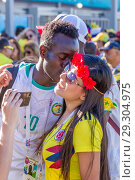Купить «Russia, Samara, June 2018: A cheerful football fan from Senegal kisses a fan from Colombia.», фото № 29304975, снято 28 июня 2018 г. (c) Акиньшин Владимир / Фотобанк Лори