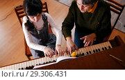 Купить «A little girl playing piano on music lesson. A teacher helping her. Upper angle», фото № 29306431, снято 6 декабря 2019 г. (c) Константин Шишкин / Фотобанк Лори