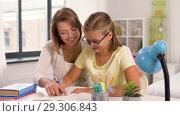 Купить «mother and daughter doing homework together», видеоролик № 29306843, снято 19 октября 2018 г. (c) Syda Productions / Фотобанк Лори