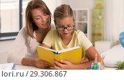 Купить «mother and daughter doing homework together», видеоролик № 29306867, снято 19 октября 2018 г. (c) Syda Productions / Фотобанк Лори