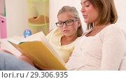 Купить «happy girl with mother reading book at home», видеоролик № 29306935, снято 19 октября 2018 г. (c) Syda Productions / Фотобанк Лори