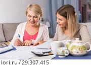 Купить «Daughter helps mother to lead home accounting», фото № 29307415, снято 13 ноября 2017 г. (c) Яков Филимонов / Фотобанк Лори