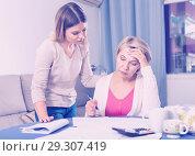 Купить «Daughter helps mother to lead home accounting», фото № 29307419, снято 13 ноября 2017 г. (c) Яков Филимонов / Фотобанк Лори