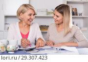 Купить «Daughter helps mother to lead home accounting», фото № 29307423, снято 13 ноября 2017 г. (c) Яков Филимонов / Фотобанк Лори
