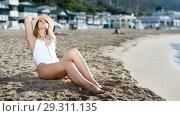 Купить «Female in swimsuit taking sunbath at sand at sea shore on sunny day», фото № 29311135, снято 10 июля 2018 г. (c) Яков Филимонов / Фотобанк Лори