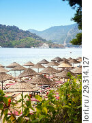 Купить «A hotel beach with lounges and  wickered sunny umbrellas», фото № 29314127, снято 11 октября 2018 г. (c) Юлия Кузнецова / Фотобанк Лори