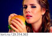 Купить «Woman bite burger and winks. Happy student eat sandwich lunch.», фото № 29314363, снято 20 марта 2019 г. (c) Gennadiy Poznyakov / Фотобанк Лори