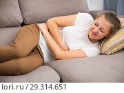 Girl is lying unhappy because she has a stomach ache. Стоковое фото, фотограф Яков Филимонов / Фотобанк Лори
