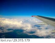 Купить «Темно-синее небо с облаками и крылом самолета», фото № 29315179, снято 5 октября 2012 г. (c) Михаил Котов / Фотобанк Лори