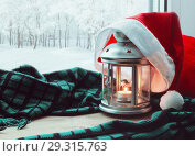 Купить «Festive tranquil Christmas and New Year still life -lantern with candle and Santa hat on the windowsill and winter park outdoor. Concept of Christmas and New Year.Christmas and New year still life», фото № 29315763, снято 25 мая 2020 г. (c) Зезелина Марина / Фотобанк Лори