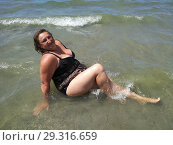 A middle-aged woman sits in the sea. Стоковое фото, фотограф Дмитрий Морозов / Фотобанк Лори