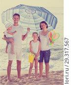 Купить «family standing under sun umbrella», фото № 29317567, снято 15 октября 2019 г. (c) Яков Филимонов / Фотобанк Лори