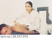 Купить «female masseur doing massage at back man who lying on a massage table in a beauty salon», фото № 29317915, снято 12 июня 2017 г. (c) Яков Филимонов / Фотобанк Лори