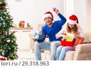 Купить «Young couple celebrating christmas at home», фото № 29318963, снято 16 июля 2018 г. (c) Elnur / Фотобанк Лори