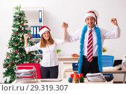 Купить «Man and woman working at the office on Cristmass eve», фото № 29319307, снято 19 июля 2018 г. (c) Elnur / Фотобанк Лори