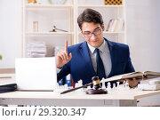 Купить «Young lawyer playing chess to train his court strategy and tacti», фото № 29320347, снято 31 июля 2018 г. (c) Elnur / Фотобанк Лори