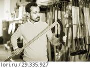 Купить «Man choosing various tools in garden equipment shop», фото № 29335927, снято 2 марта 2017 г. (c) Яков Филимонов / Фотобанк Лори