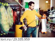 Купить «Young man choosing garden sprayer in garden equipment shop», фото № 29335959, снято 2 марта 2017 г. (c) Яков Филимонов / Фотобанк Лори