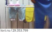 Купить «Женщина вешает ползунки на подвесную сушилку на радиаторе», видеоролик № 29353799, снято 1 ноября 2018 г. (c) Элина Гаревская / Фотобанк Лори
