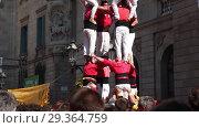 Купить «Costumed castellers make castell near ayuntamiento building during La Merca in Barcelona», видеоролик № 29364759, снято 23 сентября 2018 г. (c) Яков Филимонов / Фотобанк Лори