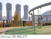 "Купить «Swing in new park ""Khodynskoe field"" against modern skyscrapers, Moscow, Russia. It opened in september of 2018.», фото № 29366271, снято 18 октября 2018 г. (c) Papoyan Irina / Фотобанк Лори"