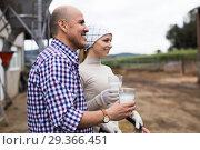 rural country couple of farmers posing with glass of milk at cowfarm. Стоковое фото, фотограф Татьяна Яцевич / Фотобанк Лори