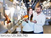 Купить «Smiling couple customers choosing bedside lamp in furniture store», фото № 29366743, снято 29 января 2018 г. (c) Яков Филимонов / Фотобанк Лори