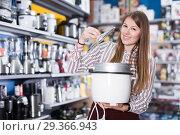 Young woman choosing slow cooker in shop. Стоковое фото, фотограф Яков Филимонов / Фотобанк Лори