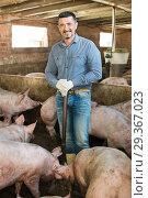 Купить «Man working on animal farm», фото № 29367023, снято 17 января 2019 г. (c) Яков Филимонов / Фотобанк Лори