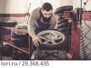 Купить «Man is working at restoring wheel», фото № 29368435, снято 9 декабря 2018 г. (c) Яков Филимонов / Фотобанк Лори