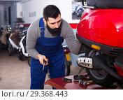 Купить «Worker inspects the motorcycle for damage», фото № 29368443, снято 11 декабря 2018 г. (c) Яков Филимонов / Фотобанк Лори