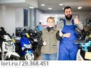 Купить «happy male worker assisting female customer in repairing motorcycle in workshop», фото № 29368451, снято 13 декабря 2018 г. (c) Яков Филимонов / Фотобанк Лори