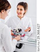 Купить «Female manicurist showing lacquer color schemes», фото № 29368627, снято 2 февраля 2017 г. (c) Яков Филимонов / Фотобанк Лори