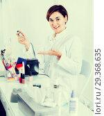 Купить «Smiling female manicurist showing her workplace», фото № 29368635, снято 2 февраля 2017 г. (c) Яков Филимонов / Фотобанк Лори
