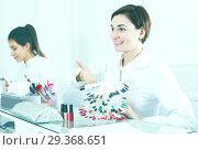 Купить «Manicurist demonstrating nail polish», фото № 29368651, снято 2 февраля 2017 г. (c) Яков Филимонов / Фотобанк Лори