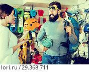 Купить «Climbers examining alpinism equipment items in sports shop», фото № 29368711, снято 24 февраля 2017 г. (c) Яков Филимонов / Фотобанк Лори