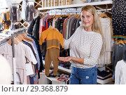Купить «Woman showing baby costumes on hanger», фото № 29368879, снято 9 октября 2018 г. (c) Яков Филимонов / Фотобанк Лори