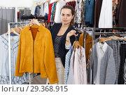 Купить «Woman holding lot of hanger with clothes», фото № 29368915, снято 10 октября 2018 г. (c) Яков Филимонов / Фотобанк Лори