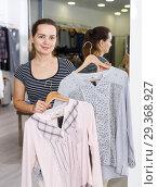Купить «Shop assistant demonstrating jacket on hanger», фото № 29368927, снято 10 октября 2018 г. (c) Яков Филимонов / Фотобанк Лори