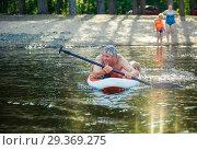 Довольный мужчина гребет веслом, лежа на сапборде. Стоковое фото, фотограф Сергей Цепек / Фотобанк Лори