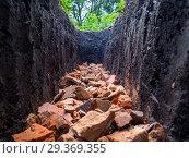 Битый кирпич, уложенный на дно выкопанной в земле траншеи. Стоковое фото, фотограф Вячеслав Палес / Фотобанк Лори